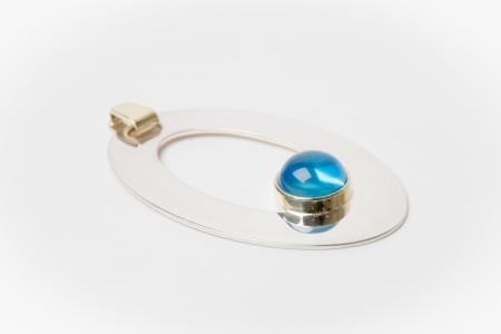 Glanzende zilveren hanger met blauwe topaas en een gouden accent